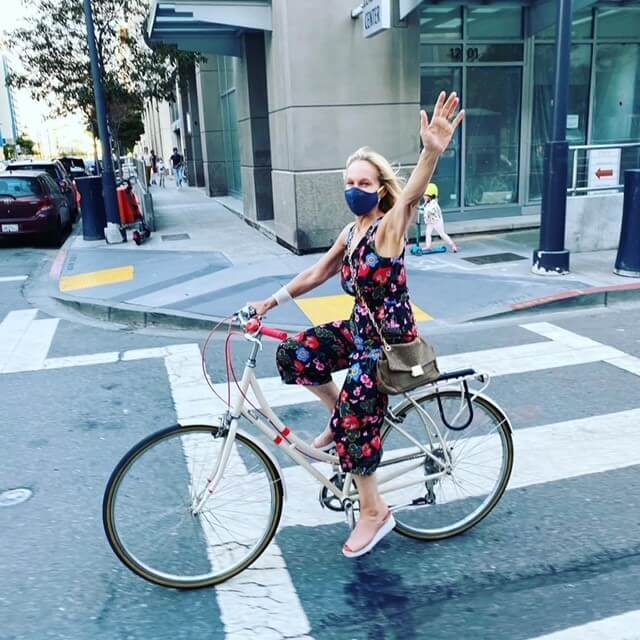 Annelaine riding her white city bike and waving in San Francisco